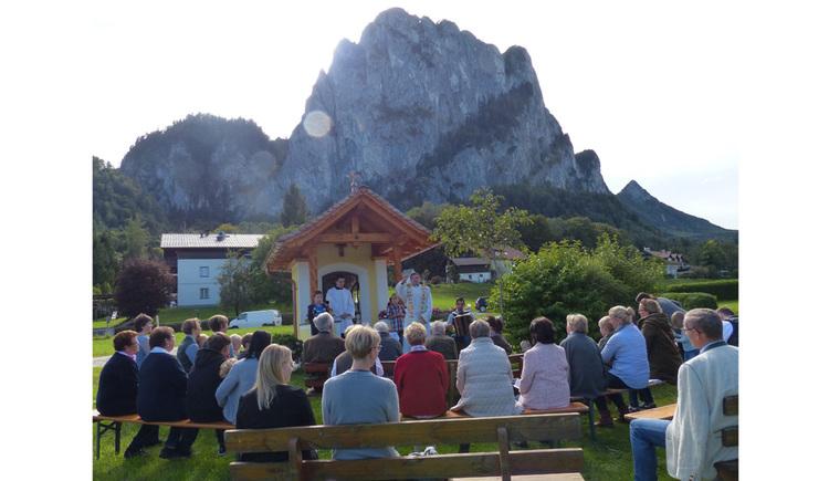 Personen sitzen auf Holzbänken, dahinter die Kapelle, im Hintergrund Berge