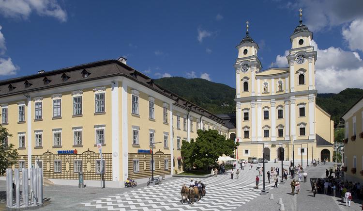 Blick vom Kirchenplatz auf die Kirche, seitlich ein Gebäude. (© Tourismusverband MondSeeLand)