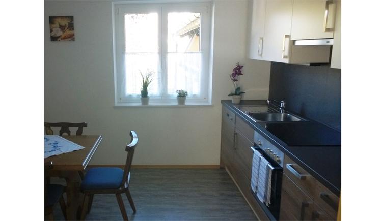 Küche mit Herd, Tisch und Stühle, im Hintergrund ein Fenster