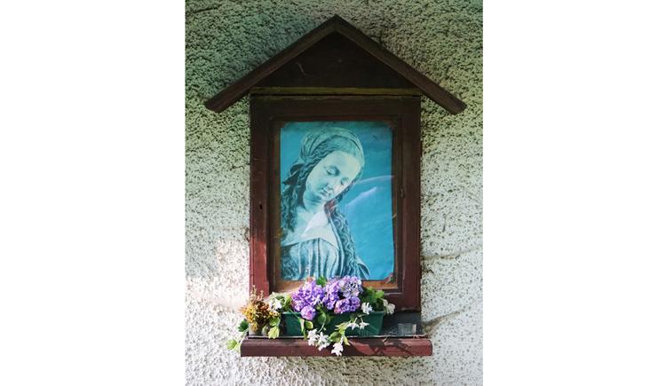 Blick auf ein Bild in einem Holzrahmen, darunter Blumen