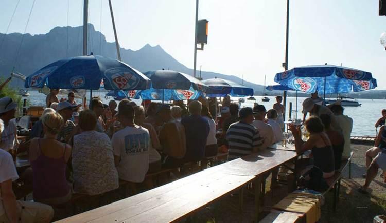Außenbereich mit Bänke und Tische; geselliges Beisammensein direkt am See; im Hintergrund die Berge. (© www.mondsee.at)