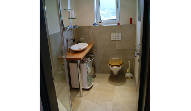 Bathroom with toilet, sink and part of the shower