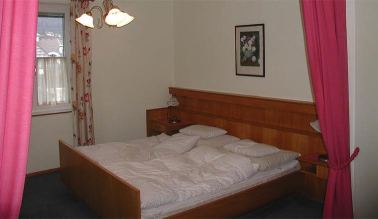 Schlafzimmer mit Doppelbett, Nachtkästchen, hinter dem Bett ein Bild, im Hintergrund ein Fenster, Teppichboden