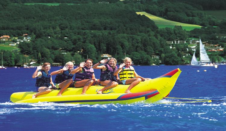 Kinder werden auf einem Bananenboot auf dem See gezogen, im Hintergrund Landschaft