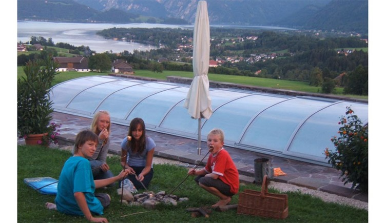 Children sit in the meadow, behind the covered pool, in the background view of the lake. (© Nußbaumer)
