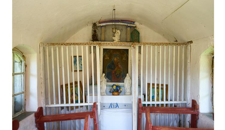 seitlich Holzbänke, im Vordergrund ein Altar mit Heiligenfiguren, Blumen