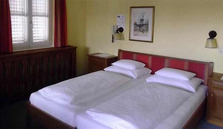 Schlafzimmer mit Doppelbett, Nachtkästchen, hinter dem Bett ein Bild und Telefon auf der Wand, seitlich ein Fenster