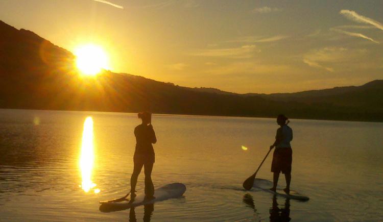 Personen auf einem SUP-Board im See