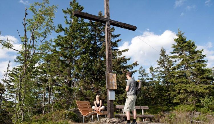 Junges Pärchen auf einem Aussichtsfelsen mit Gipfelkreuz. (© Ferienregion Böhmerwald | Weissenbrunner)