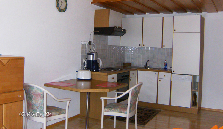 im Vordergrund ein Tisch mit Stühlen, Toaster, im Hintergrund die Küche mit Kaffeemaschine, Herd, Spüle, Geschirrspüler