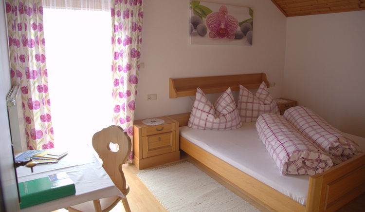 Bedroom with double bed, bedside tables and a small table with chair