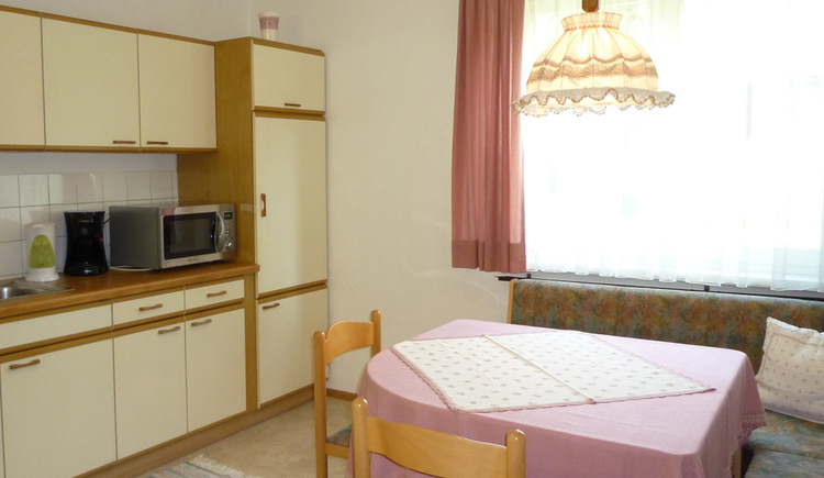 Fully equipped kitchen with coffee maker, microwave and cozy corner seat
