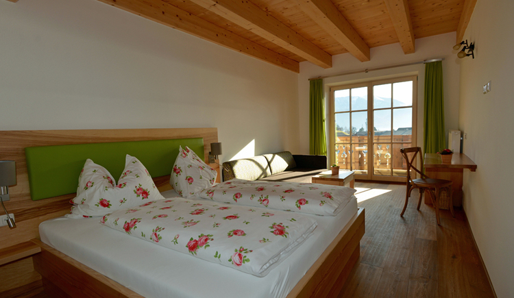 Doppelbett im Zimmer mit Holzdecke und Blick aus dem Fenster