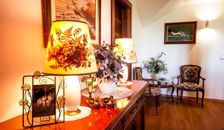 Vorraum mit Kommode darauf Fotos und Lampen blumen, im Hintergrund ein kleiner Tisch mit Blumen und Stühle, Bild an der Wand