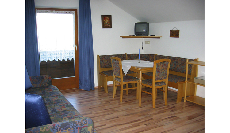 Dining area with corner bench, table and chairs, couch, in the background a balcony door