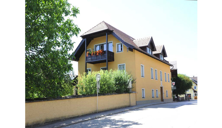 Blick auf das Haus, seitlich davor eine Steinmauer, Bäume, Straße. (© Schwaighofer)