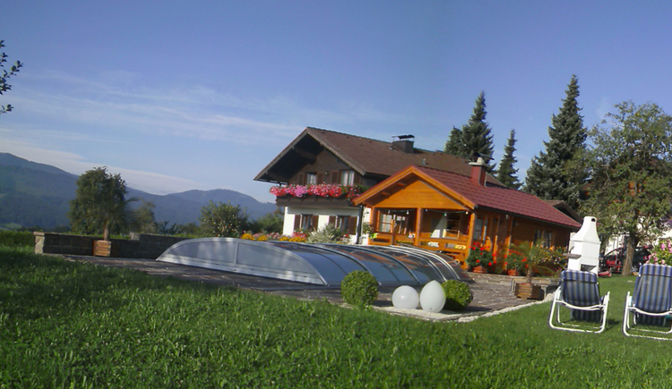 View of the covered pool, on the side sun lounger in the meadow, in the background the holiday farm. (© Nußbaumer)