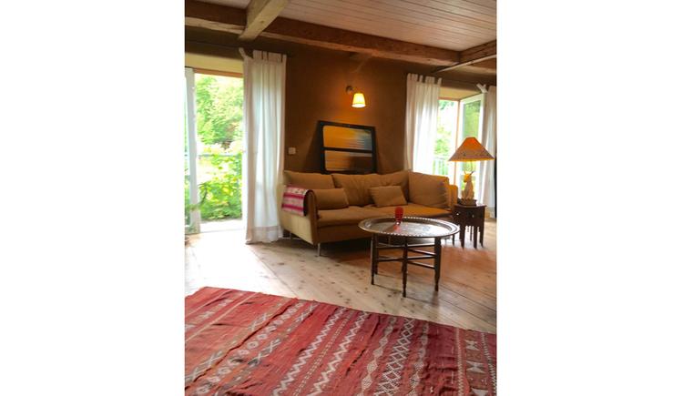 Wohnbereich, im Hintergrund Balkontüren, Couch, Beistelltisch mit Lampe, im Vordergrund ein Teppich