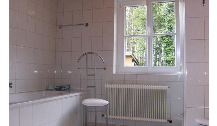 Badezimmer mit Badewanne, Hocker, im Hintergrund ein Fenster