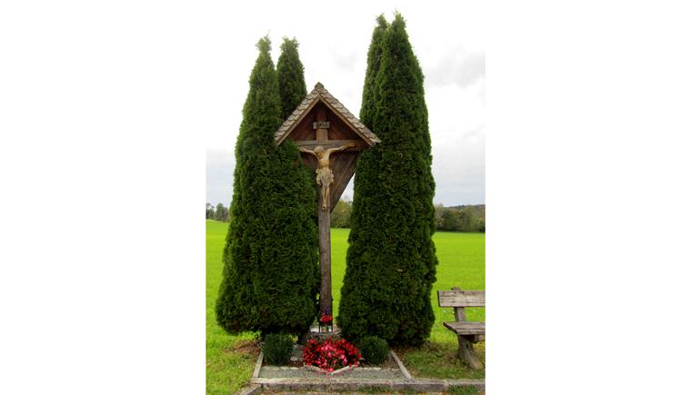 Blick auf ein Holzkreuz zwischen zwei Bäume