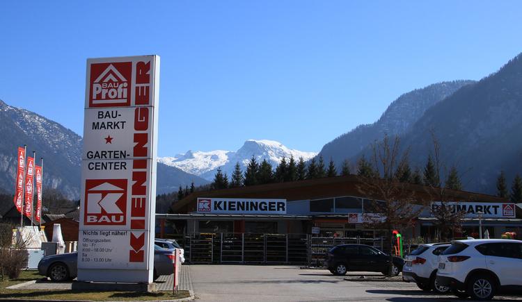 Front view of do-it-yourself-store Baumarkt Kieninger with car park - left tablet of Baumarkt Kieninger - background mountain Krippenstein