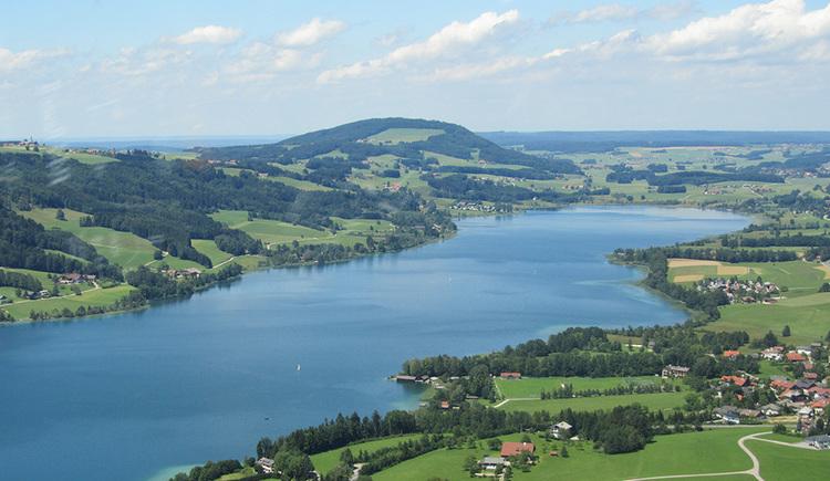 Vom Hubschrauber aus Blickrichtung Nordwesten über den Irrsee fotografiertes Bild. Im Vordergrund Gehöfte der Gemeinde Zell am Moos, im Hintergrund der Irrsberg und Blick ins Salzburger Land.