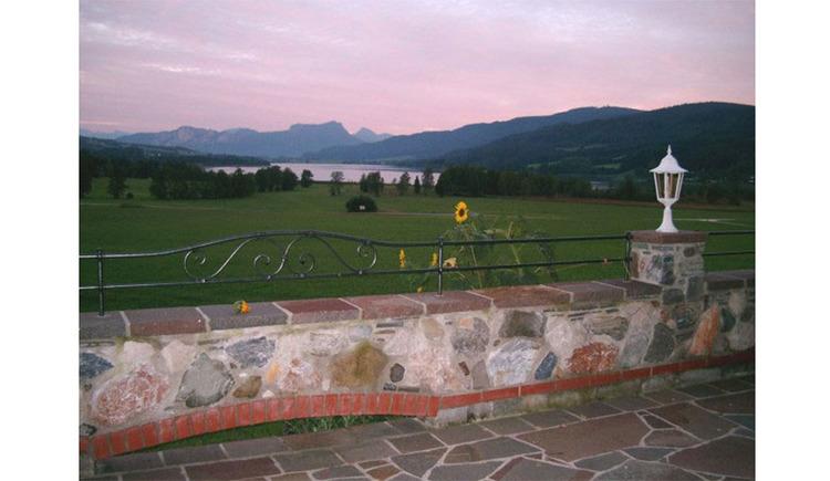 Blick von der Terrasse auf die Landschaft, im Hintergrund der See und die Berge