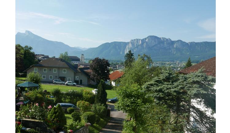 Aussicht vom Balkon auf die Wiesen, Häuser, Bäume, die Kirchtürme von der Basilika St. Michael, im Hintergrund die Berge,