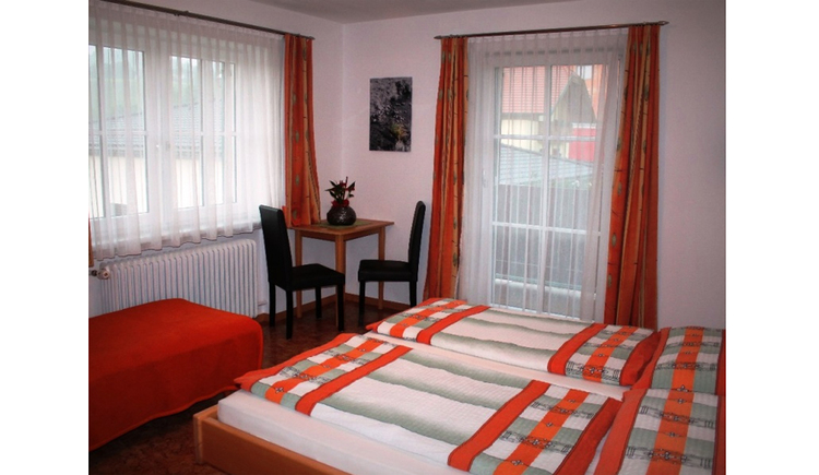 Bedroom with double bed, in the background a table and 2 chairs, window and balcony door