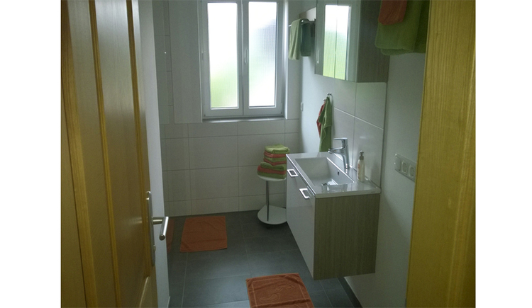 Bathroom with sink, mirror cabinet, towels, in the background window