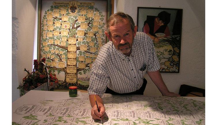 Stammbaummaler Franz bei der Arbeit, im Hintergrund ist ein fertiger Stammbaum