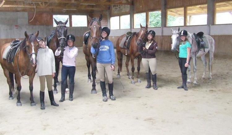 Kinder mit Pferden in der Halle