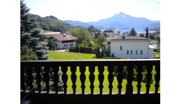 View from the balcony to the countryside, houses, forest, in the background the lake and the mountains