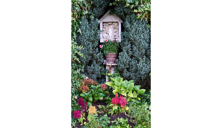 Blick auf den Bildstock, darunter und im Vordergrund Blumen und Pflanzen