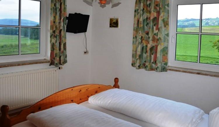 Schlafzimmer mit Doppelbett, im Hintergrund auf der Wand ein Fernseher