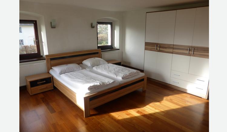 Doppelbett, Nachtkästchen, Fenster, seitlich ein Kleiderschrank
