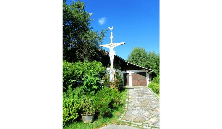 Blick auf das große Kreuz, seitlich Sträucher, im Hintergrund ein Haus