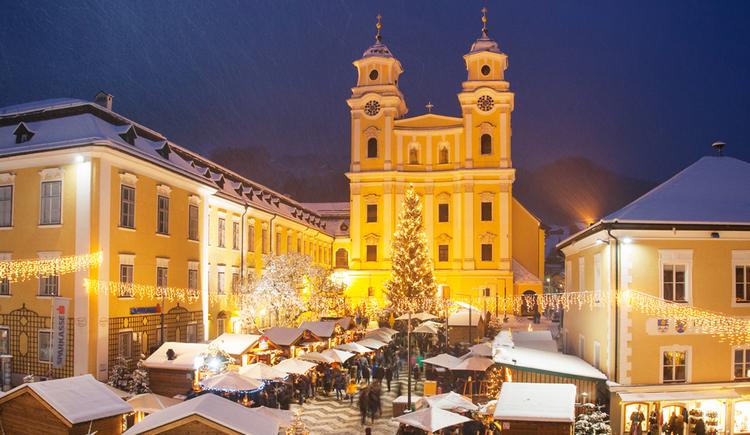 Traditioneller Adventmarkt mit verschneiten Huetten vor der Basilika St. Michael in Mondsee