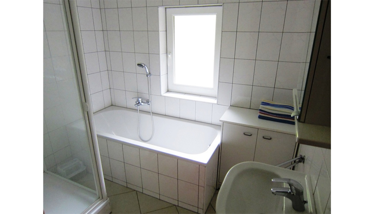 On the side a sink, behind it a small cupboard, beside it a bathtub, part of the shower sideways, in the background a window.