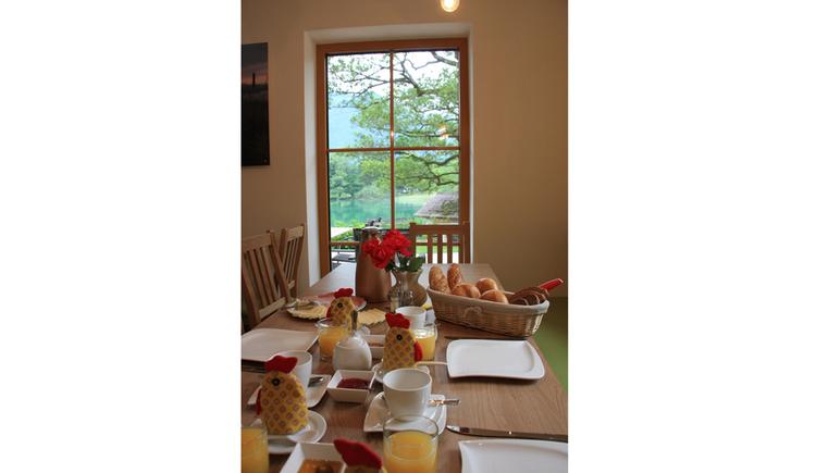 gedeckter Frühstückstisch, mit gefüllten Brotkorb, Wurst- und Käseplatte, Eier, Marmelade, Blumen, im Hintergrund eine Balkontür mit Blick auf den See