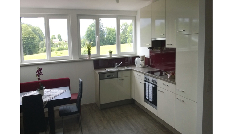 View of the kitchen with dishwasher, stove, coffee maker, water cooker, side bench - table and chairs, in the background window with garden view