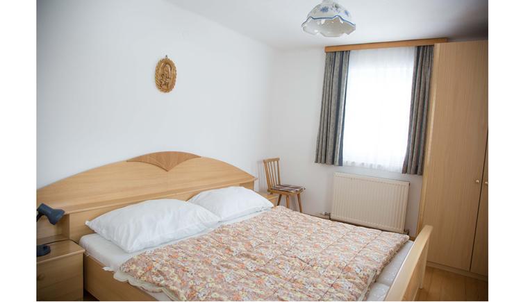 Schlafzimmer mit Doppelbett, Kleiderschrank, im Hintergrund ein Fenster