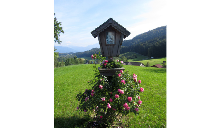 Blick auf ein Holzmarterl in einer Wiese, darunter Rosen