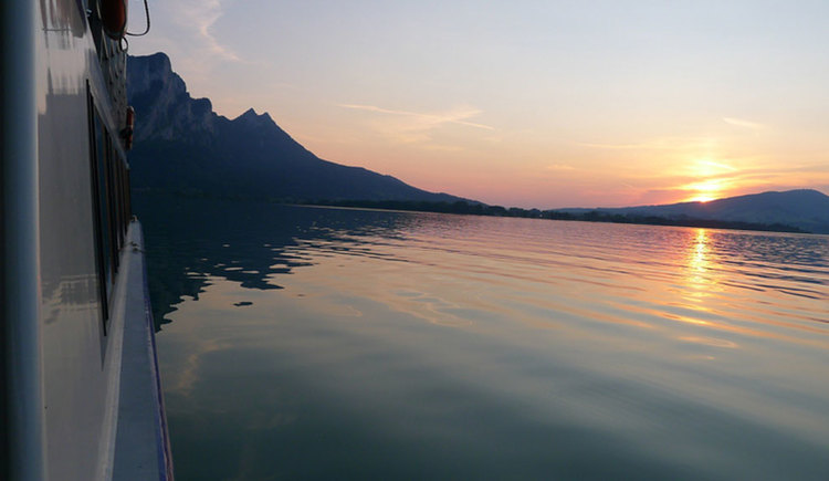 View from a boat across lake Mondsee in the direction of a sunset