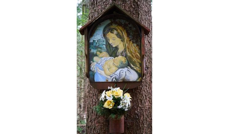 Blick auf ein Holzmarterl mit Marienbild an einem Baum, darunter Blumen in einer Vase