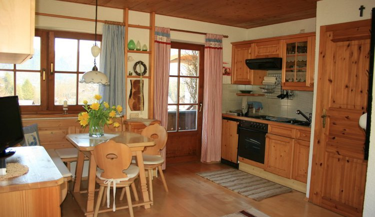 Die komplett ausgestattete Küche mit gemütlicher Eckgarnitur aus Holz lädt zum Verweilen ein