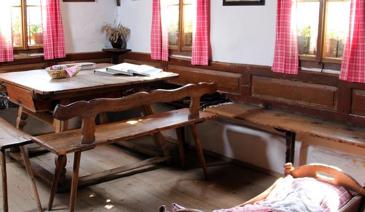 Die Wohnstube für alle Hausbewohner, ein gemeinsamer großer Eßtisch, ein alter Ofen mit eisernen Füßen und Ofenstangen zum Kleidertrocknen. Die Fenster nachträglich vergrößert. Die Seite zum Vorhaus zeigt zahlreiche Kalkschichten über dem Lehm auf den Holzbalken. Eine schöne, ortsübliche Riemlingsdecke mit starken Tramen, breiten Brettern, deren Stöße mit Riemlingen abgedeckt sind. Ledersofa, Tisch und Bank aus dem Jahr 1875. Der Herrgottswinkel, rotkarierte Schlaufenvorhänge auf Holzstangen. (© Degn Film)