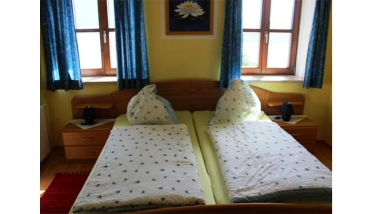 Schlafzimmer mit Doppelbett, Nachtkästchen, Tischlampe, im Hintergrund Fenster