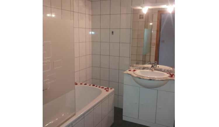 Badezimmer mit Badewanne, im Hintergrund ein Waschbecken