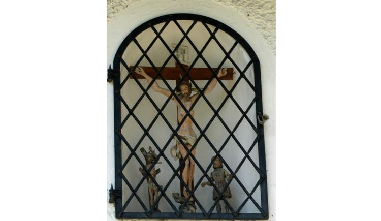 Blick durch ein Gitter auf ein Kreuz, Heiligenfiguren
